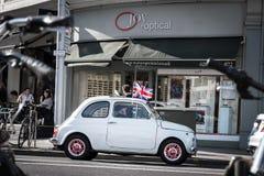 London Förenade kungariket - lilla fiat med en brittisk flagga på taket kör till och med London gator arkivbild