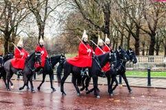 London Förenade kungariket - 11/04/2016: Ståta den kungliga vakten på svarta hästar på gatan i London, efter regn, i bakgrunden l Royaltyfria Bilder