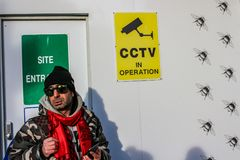 LONDON - FEB 16, 2018: An unidentified man with red scarf and sunglasses next to CCTV Camera Video surveillance sign on site wall royalty free stock photos