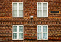 London, four white windows on red bricks. Traditional facade of a building in London Royalty Free Stock Photo