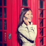 London-Frau am intelligenten Telefon durch rote Telefonzelle Stockbild