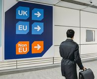 Passenger walks past sign prior to immigration control pass a sign pointing towards queues for UK, EU and Non-EU. London Gatwick, March 2nd, 2018: Passenger royalty free stock photography