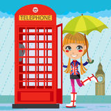 London Girl. Young girl opening a red telephone booth in London Royalty Free Stock Photos