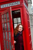 London girl. Young woman by red phone booth. Portrait of beautiful smiling happy young woman standing in London. England, Great Britain. White  Young woman Royalty Free Stock Image