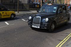 Cabs in London traffic. LONDON, GREAT BRITAIN, April 21, 2018 : Hackney carriage or Black Cab in the streets of London. In the United Kingdom, the name hackney Royalty Free Stock Images
