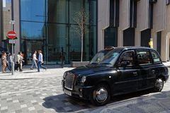 Black Cab in a business district. LONDON, GREAT BRITAIN, April 20, 2018 : Hackney carriage or Black Cab. In the United Kingdom, the name hackney carriage today stock photos