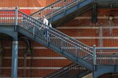 Man on a metallic stair in front of a brick wall Royalty Free Stock Photo