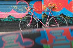 Pink bike on the wall. LONDON, GREAT BRITAIN, April 22, 2018 : Pink bike in front of a graffiti on the walls of Soreditch, with reflection on the roof of a car stock photography