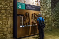 The Armory Hall of the Tower of London. LONDON, GREAT BRITAIN - MAY 16, 2014:Unidentified tourists are considering a stand with early medieval weapons in the Royalty Free Stock Image