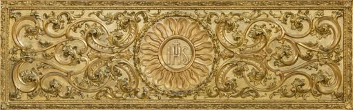LONDON, GREAT BRITAIN - SEPTEMBER 18, 2017: The carved polychrome baroque relief with the IHS initials on the altar in church Our Stock Photo