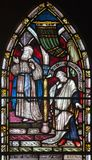LONDON, GREAT BRITAIN - SEPTEMBER 19, 2017: The parable The Prayers of Pharisees and Tax Collectors in the temple. On the stained glass in St Mary Abbot`s royalty free stock image