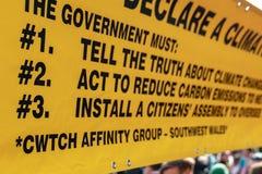 London, Großbritannien - 15. April 2019: Gelbe Fahne der Löschungs-Aufstandsaktivisten von drei Kernnachfragen nach der Regieru lizenzfreies stockbild
