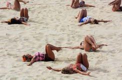 London, Großbritannien, im August 2012 Frauengruppe, die exercice auf einem Strandsalvengericht tut Stockbilder