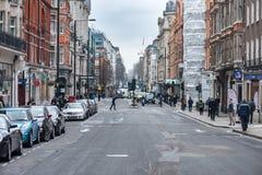 LONDON, GROSSBRITANNIEN - 9. APRIL 2013: Beschäftigte alte Stadtstraße mit gehenden Völkern stockfotografie