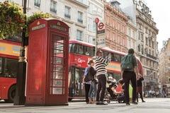 LONDON, GROSSBRITANNIEN - 4. AUGUST 2016: Touristen durch ikonenhaften roten Bus und Rot stockfotografie
