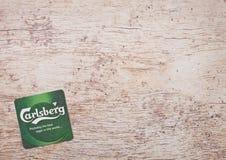 LONDON, GROSSBRITANNIEN - 22. MÄRZ 2018: Carlsberg-Bier beermat Küstenmotorschiff auf Holz Lizenzfreie Stockfotografie