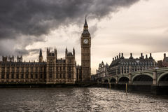 London - The Houses of Parliament, the Big Ben and Westminster Bridge under dark clouds Royalty Free Stock Images