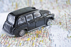 London iconic black cab. On a map with London city in focus stock images