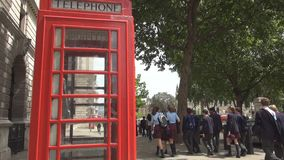 London image with red phone booth on sidewalk and tourists strolling on streets.  stock footage