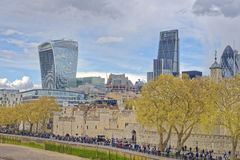 London. Image taken of people waiting on a tree-lined street to enter the tower of london with modern office blocks in the background including the walkie-talkie Royalty Free Stock Images