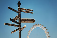 London indications. Indications in London for tourists with the London Eye at the background stock photography