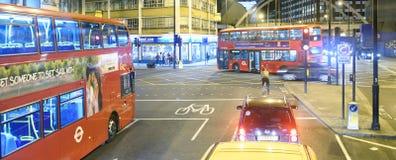 LONDON - 2. JULI 2015: Rote Busse entlang Stadtstraßen Sie sind a Lizenzfreie Stockbilder