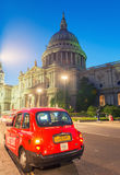 LONDON - JUNE 12, 2015: Red cab under Saint Paul Cathedral at ni Royalty Free Stock Photos