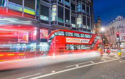 LONDON - JUNE 14, 2015: Red Double Decker Bus speeds up in city. Streets at night. These modern buses came to replace an old classic,the AEC Routemaster Royalty Free Stock Image