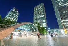 LONDON - JUNI 14, 2015: Ljus av Canary Wharf byggnader på nigh Royaltyfri Foto