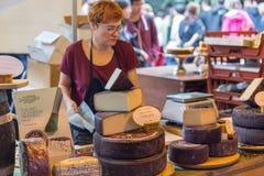 LONDON - JUNI 12, 2015: Ost shoppar i London En variation av ostar som är till salu på stadmarknaden i London, Förenade kungarike Arkivbild