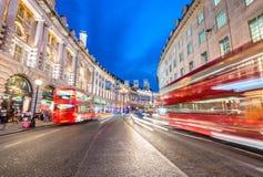 LONDON - JUNI 14, 2015: Röda dubbla Decker Bus hastigheter upp i stad Arkivfoton