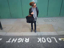 When in London look right!. Young girl looking at wrong side on the street Stock Image