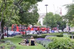 LONDON - MAI 2015: Rote Busse entlang Stadtstraßen Sie sind ein majo Lizenzfreie Stockbilder