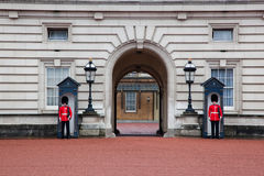 LONDON - MAJ 17: Brittiska kungliga vakter bevakar ingången till Buckingham Palace på Maj 17, 2013 Arkivfoton