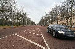 London Mall Fast Car. Car speeding by on the Mall in London weather, Buckingham Palace in the distance Royalty Free Stock Photography