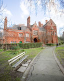 London mansion. Wide angle view of an old red brick Victorian mansion with a path and bench leading to its entrance Royalty Free Stock Images