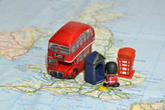 London on map of England with miniature souvenirs. Miniature souvenir toys - national symbols of English culture - red double-decker bus, Royal Guard, blue red Stock Photography