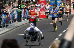 2013 London Marathon. London, UK - April 21, 2013: Wheelchair racing contestants in the crowds of London Marathon runners. The London Marathon is next to New Stock Images