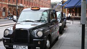 Close up shot of a black London taxi cab waiting at a taxi rank outside of King`s Cross St. Pancras Railway Station