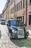 LONDON - MAY 2013: Black cab along old city street. London attra Stock Images