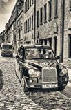 LONDON - MAY 2013: Black cab along old city street. London attra Stock Photos