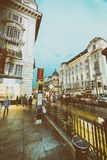 LONDON - MAY 2015: Tourists along Piccadilly Circus at sunset. T. He city attracts 30 million visitors annually Stock Photo