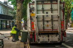 Worker of urban municipal recycling garbage collector truck loading waste and trash bin royalty free stock image