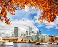 London med den moderna staden mot höstsidor i England, UK arkivfoto