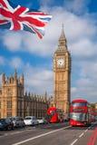 London med röda bussar mot Big Ben i England, UK arkivfoton