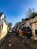 A London mews with abandoned cars and a skip that with rubbish. Stock Photos