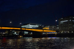 London by night by River Thames. LONDON, UNITED KINGDOM - SEPTEMBER 11 2015: London by night by River Thames, with orange bridge Royalty Free Stock Photo