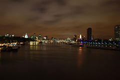 London night view of the thames. With boats and dramatic sky Royalty Free Stock Photography