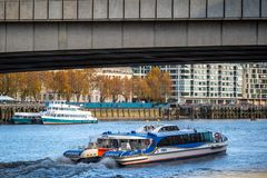City cruises sightseeing tour boat sails on the Thames River. LONDON - NOVEMBER 13 : A city cruises tour sails on the Thames River sightseeing boat goes under stock images
