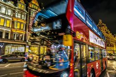 Night view with red double decker bus on moving in front of Harr. LONDON - NOVEMBER 29, 2017: Night view with red double decker bus on moving in front of Harrods Stock Photography